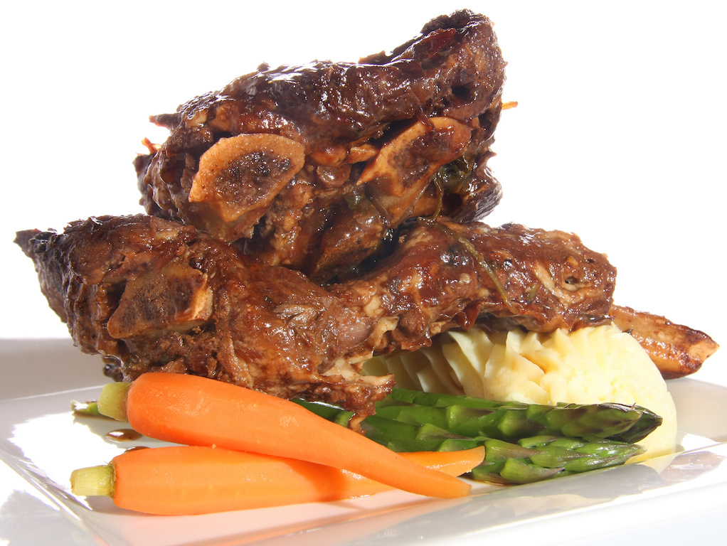 Beef ribs with mashed potatoes, carrots and asparagus.