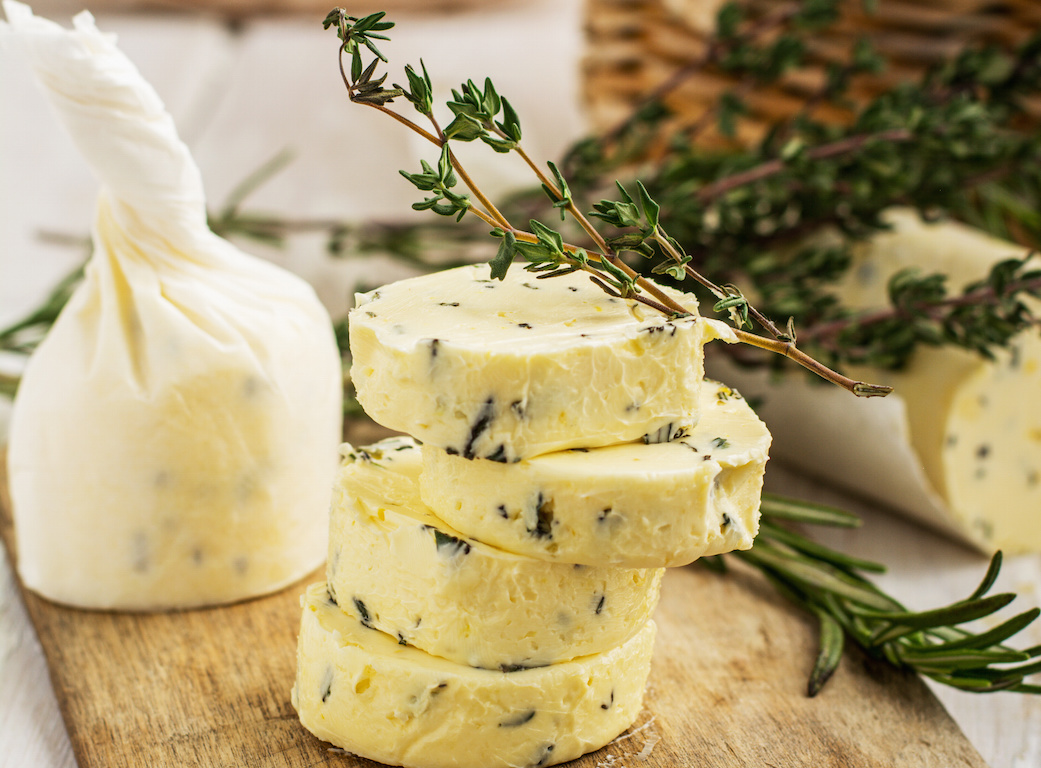 Butter with thyme and rosemary and lemon zest. Sliced on a wooden board with herbs. selective Focus