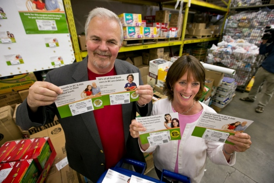 The Mustard Seed's Brent Palmer and Gayle Ireland of the Goldstream Food Bank Society hold coupons.